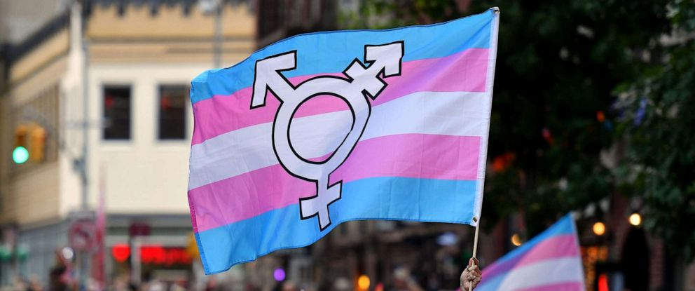 PHOTO: A person holds a transgender pride flag as people gather on Christopher Street outside the Stonewall Inn for a rally to mark the 50th anniversary of the Stonewall Riots in New York, June 28, 2019.