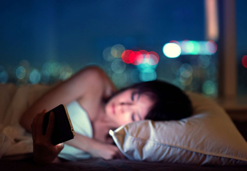 PHOTO: Women in bed at night using her smartphone.