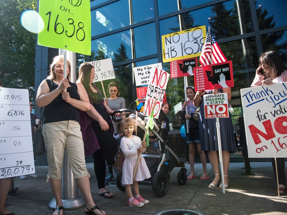religion PHOTO: A group of anti-vaccine protesters gather in front of Vancouver City Hall prior to the signing of HB 1638 in Vancouver Wash., on May 10, 2019.