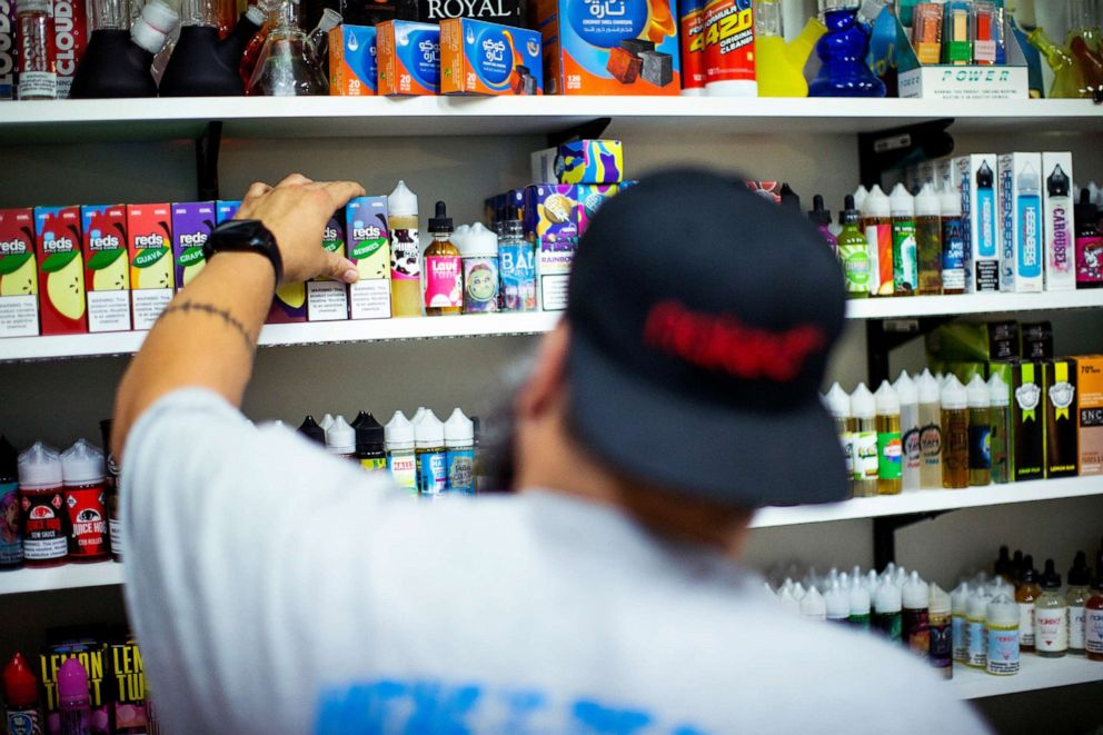 PHOTO: A vape shop worker organizes electronic smoking products in a local store in Jersey City, N.J., Sept. 12, 2019.