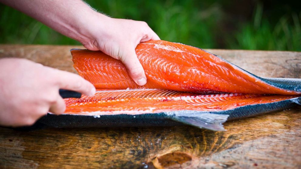 A person fillets a freshly caught wild salmon in an undated stock photo.