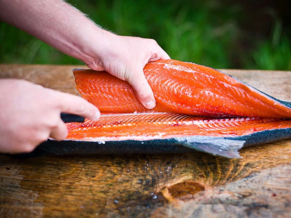 PHOTO: A person fillets a freshly caught wild salmon in an undated stock photo.