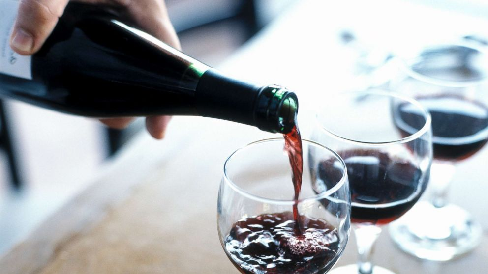 A person is pictured pouring red wine.