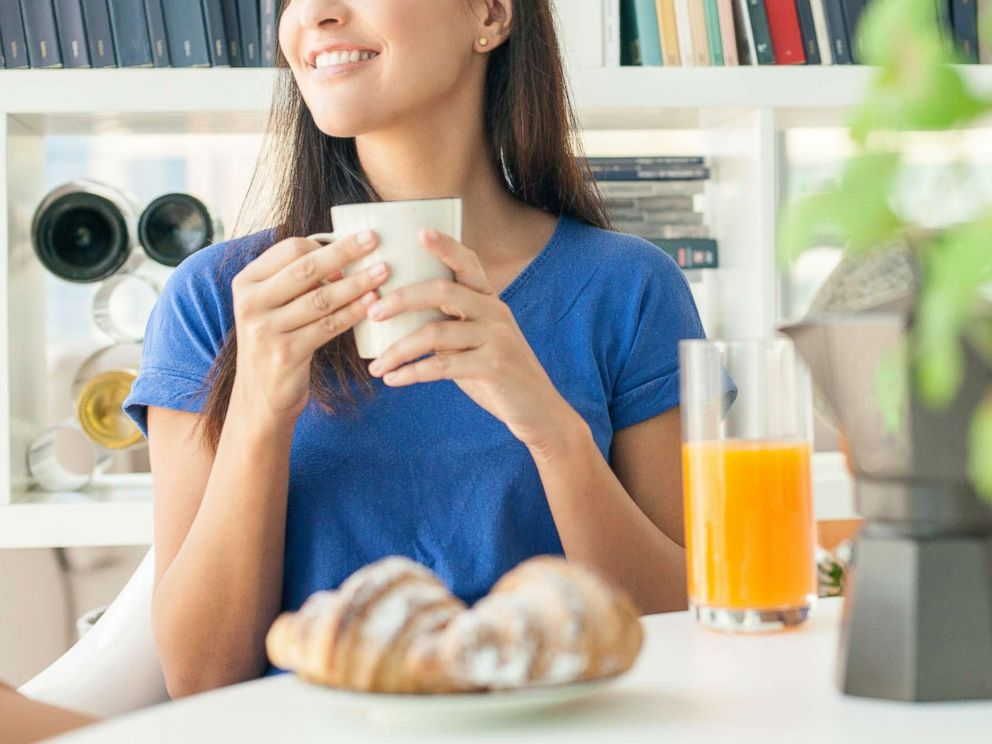 PHOTO: In this undated stock photo, a young woman having breakfast at home.