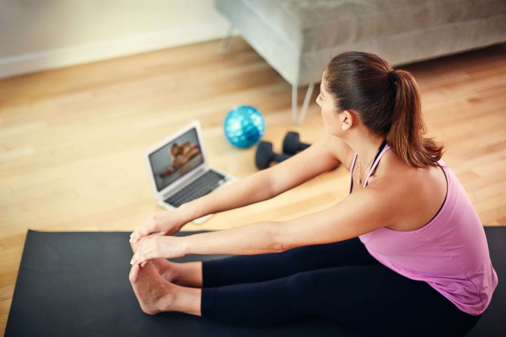 PHOTO: Woman using laptop to exercise at home.