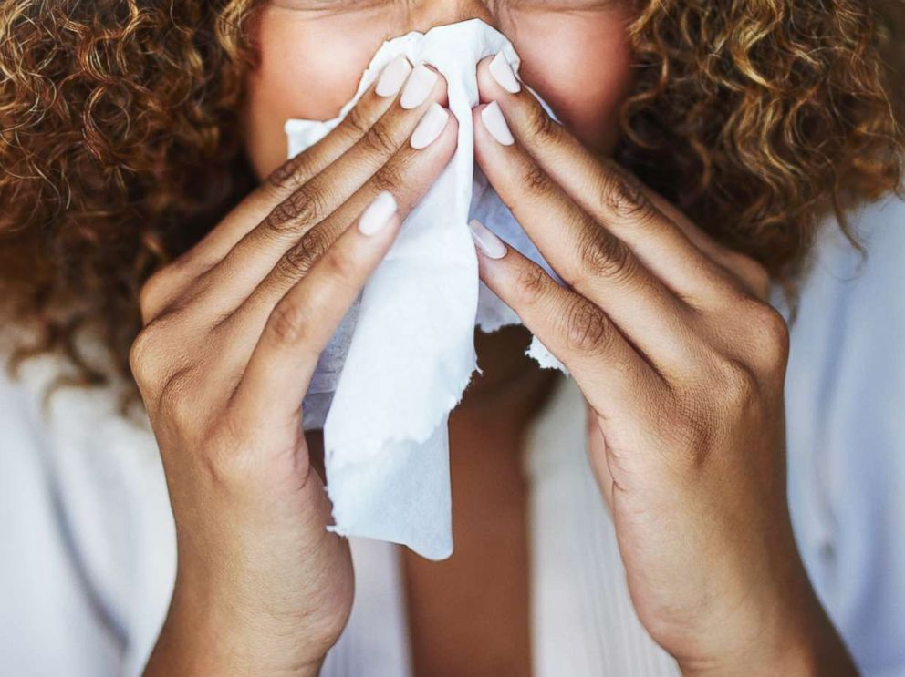 PHOTO: A woman uses a tissue to sneeze in this undated stock photo.