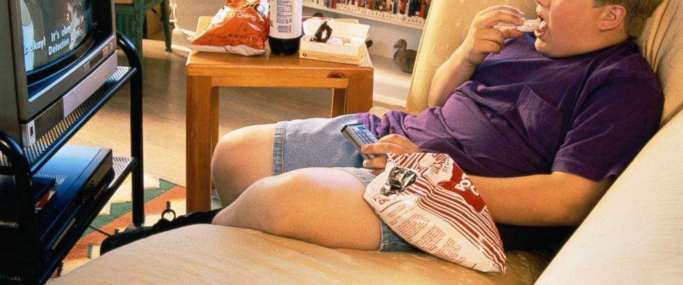 PHOTO: In this undated stock photo, a boy eats junk food while watching tv.