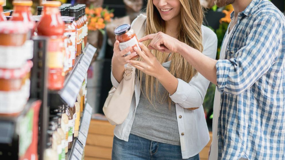 A couple grocery shopping at the supermarket looking at the nutritional content on a jar, in this undated stock photo.