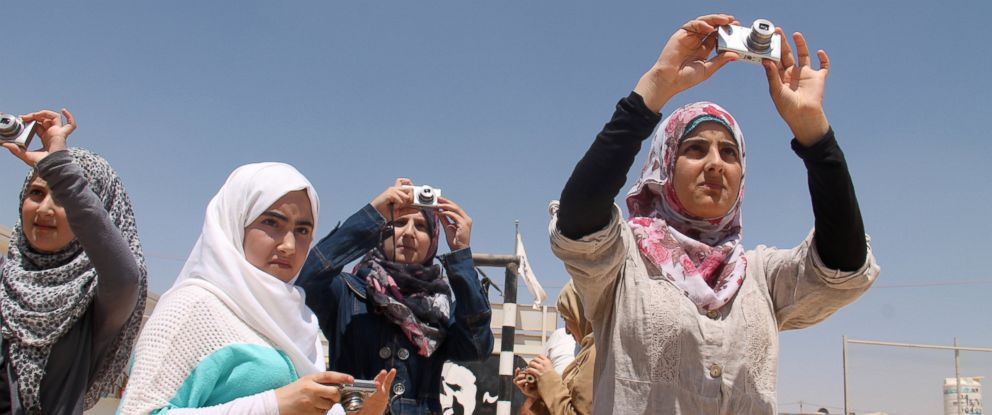 PHOTO: Syrian refugees in the Zaatari refugee camp take pictures.