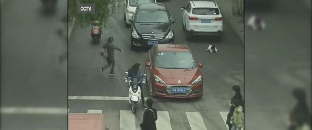 VIDEO: Shocking surveillance video shows 2-year-old dash out into the street and get run over by two cars in China before being rescued by her grandmother.