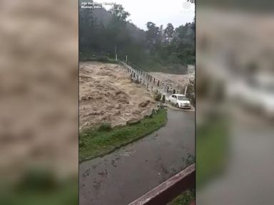 WATCH:  Vehicles cross bridge surrounded by rushing floodwaters
