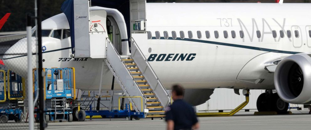 PHOTO: A worker walks next to a Boeing 737 MAX 8 airplane parked at Boeing Field in Seattle, March 14, 2019.