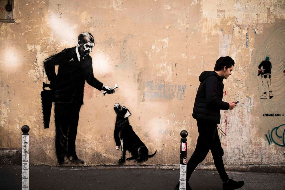 PHOTO: A man walks past a recent artwork by street artist Banksy in Paris on June 24, 2018.