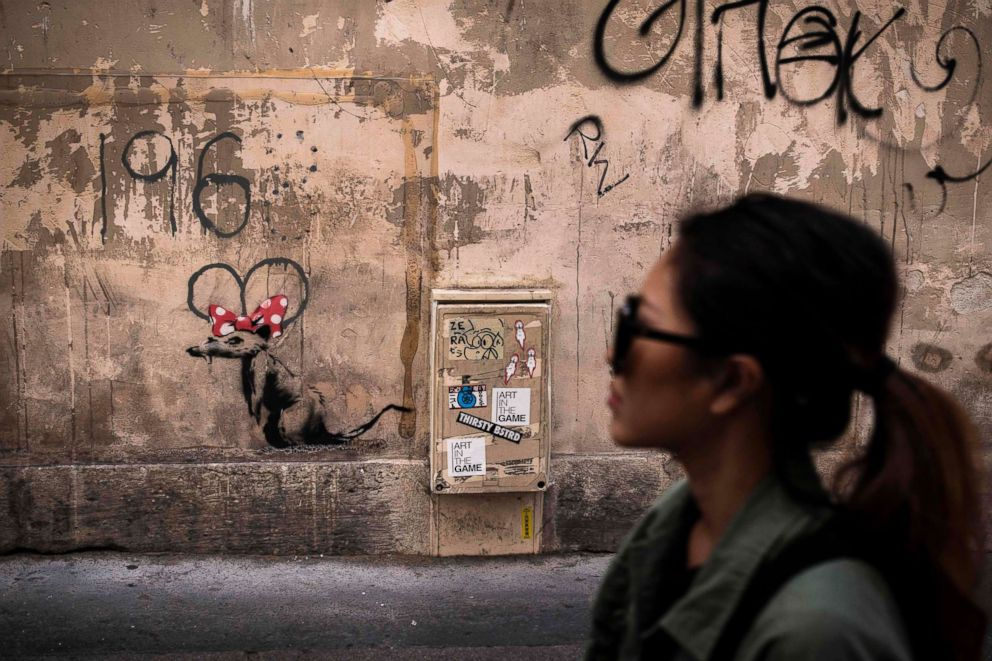 PHOTO: A woman walks past a recent artwork by street artist Banksy in Paris on June 25, 2018.