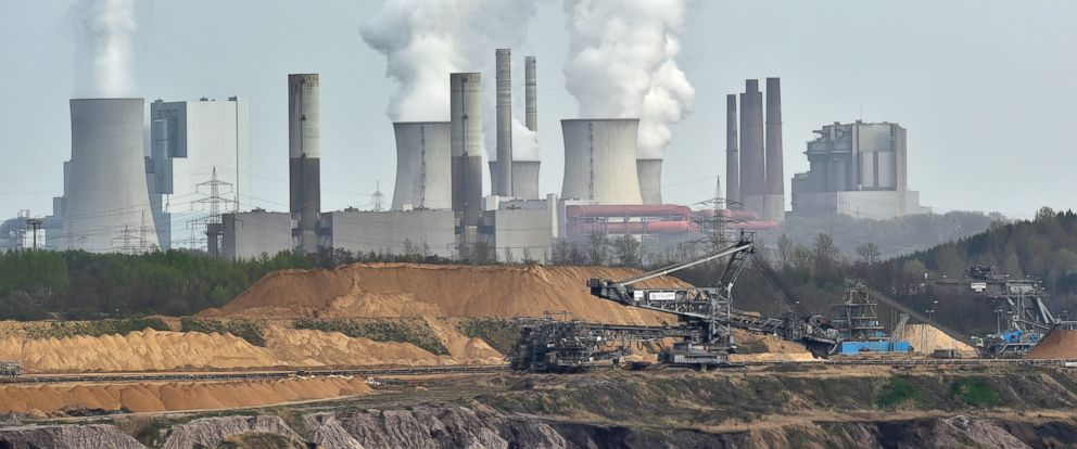 PHOTO: In this April 3, 2014 file photo, giant machines dig for brown coal at the open-cast mining Garzweiler in front of a smoking power plant near the city of Grevenbroich in western Germany.