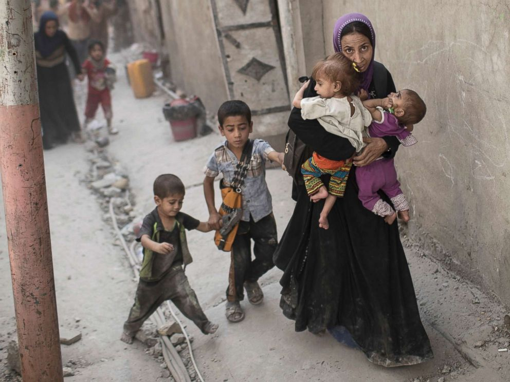 PHOTO: Iraqi civilians flee through an alley as Iraqi Special Forces continue their advance against Islamic State militants in the Old City of Mosul, Iraq, July 3, 2017.