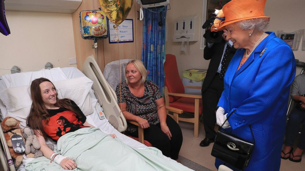 Britain's Queen Elizabeth II. right,  speaks to Millie Robson, 15, and her mother, Marie, as she visits the Royal Manchester Children's Hospital in Manchester England, to meet victims and to thank members of staff who treated them, May 25, 2017.