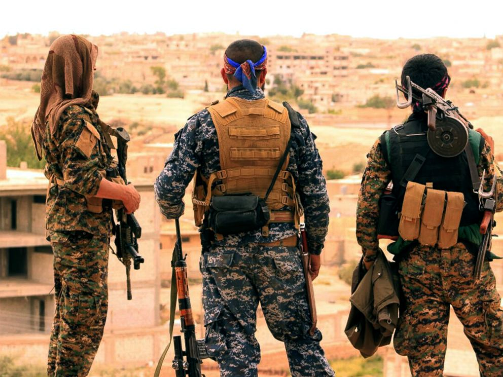 PHOTO: Fighters from the SDF look toward the northern town of Tabqa, Syria.