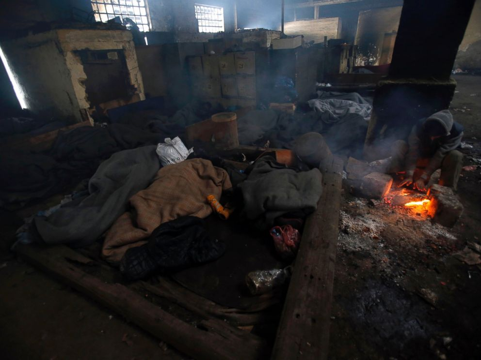 PHOTO: A migrant tries to warm up by a fire inside a crumbling warehouse that has served as a make-shift shelter for hundreds of men trying to reach Western Europe in Belgrade, Serbia, Jan. 12, 2017.