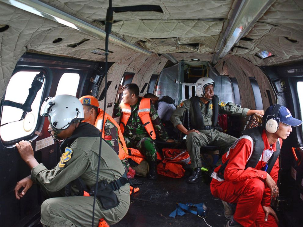 PHOTO: Crew members of an Indonesian Air Force Super Puma helicopter of the 6th Air Squadron look out of the windows during a search operation for the victims of AirAsia Flight 8501 over Java Sea, Indonesia, Jan. 1, 2015.