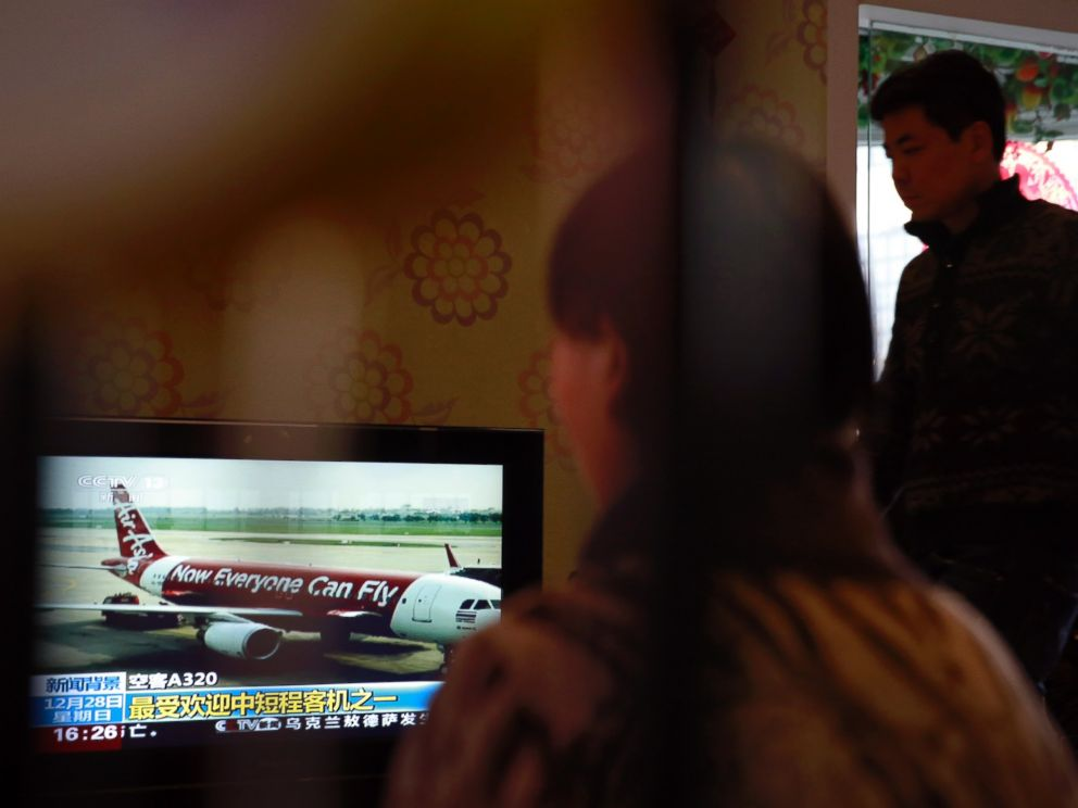 Relatives of passengers onboard the Malaysia Airlines Flight 370 that went missing on March 8, 2014, watch TV news about missing AirAsia flight QZ8501, during their year-end gathering at a house in Beijing, China Sunday, Dec. 28, 2014.