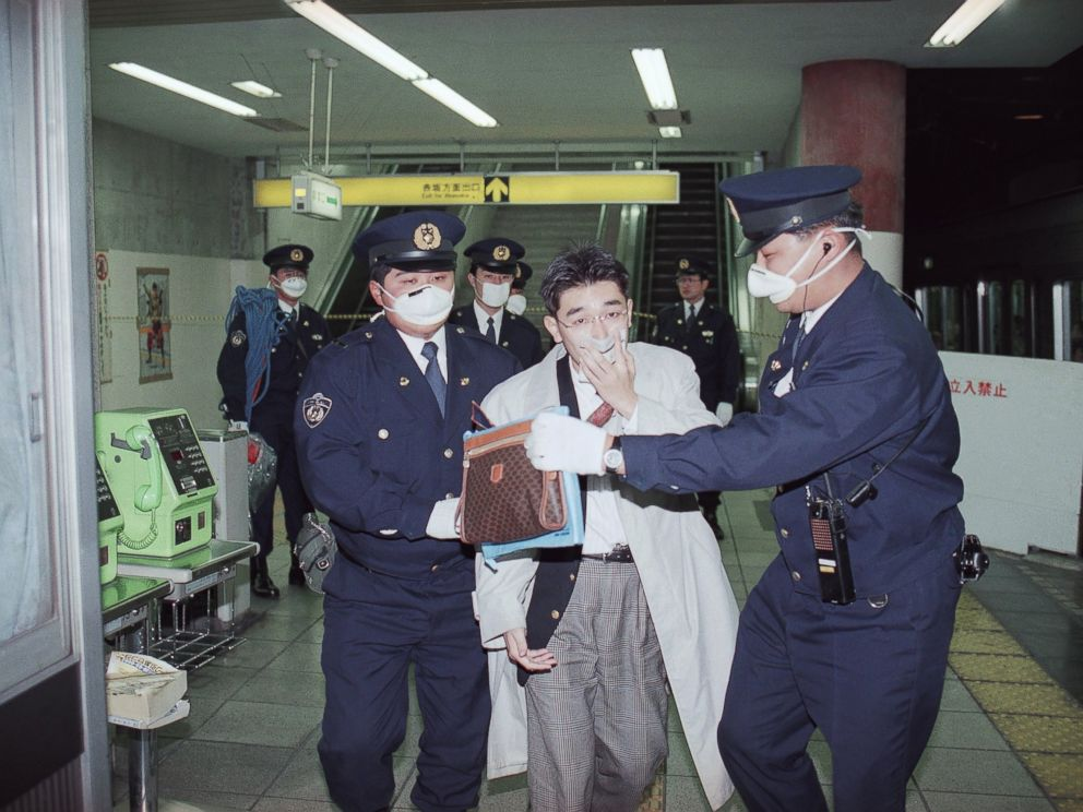 PHOTO:In this file photo, a subway passenger with his mouth covered up by a handkerchief is escorted by masked policemen from Tokyos Akasaka Station as the station was filled by toxic fumes, March 20, 1995.