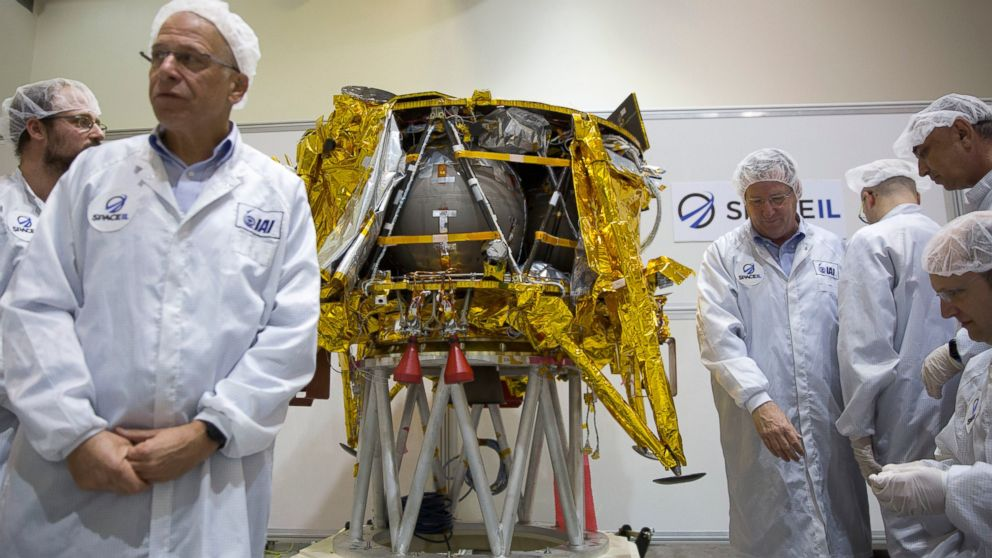 In this Monday, Dec. 17, 2018 file photo, technicians stand next to the SpaceIL lunar module, an unmanned spacecraft, on display in a special clean room during a press tour of their facility near Tel Aviv, Israel.