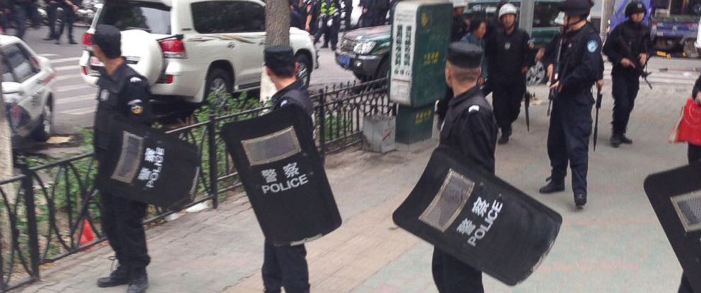 PHOTO: Police officers stand guard near a blast site in downtown Urumqi, capital of northwest Chinas Xinjiang Uygur Autonomous Region, May 22, 2014.