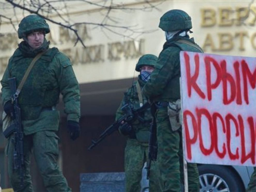 PHOTO: Unidentified gunmen wearing camouflage uniforms block the entrance of the Crimean Parliament building in Simferopol, Ukraine, Saturday, March 1, 2014. Poster reads Crimea Russia.