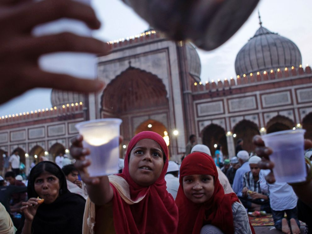 PHOTO: Muslim girls stretch their hands out to receive water after breaking fast at Jama Masjid ahead of Eid al-Fitr in New Delhi, Aug 8, 2013. Eid al-Fitr marks the end of the holy month of Ramadan, during which Muslims fast from sunrise to sunset.