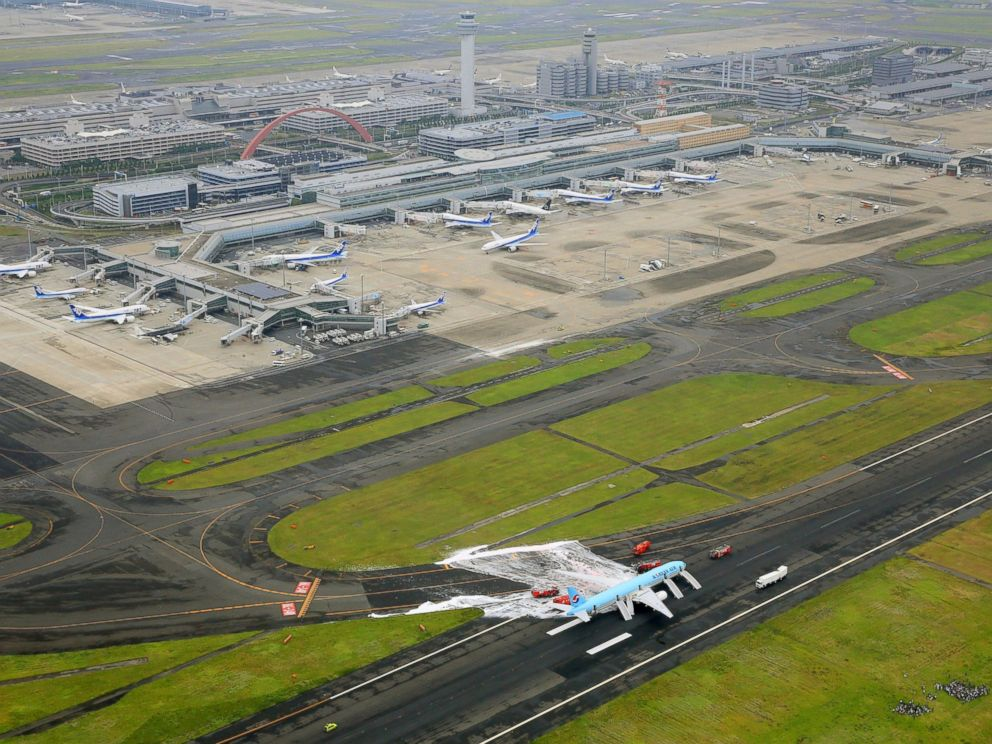 PHOTO: White form sprayed over the left engine of a Korean Air jet is seen after firefighters battled an apparent engine fire on the tarmac as passengers and crew members, bottom right, huddle on a grassy area at Haneda Airport in Tokyo May 27, 2016.