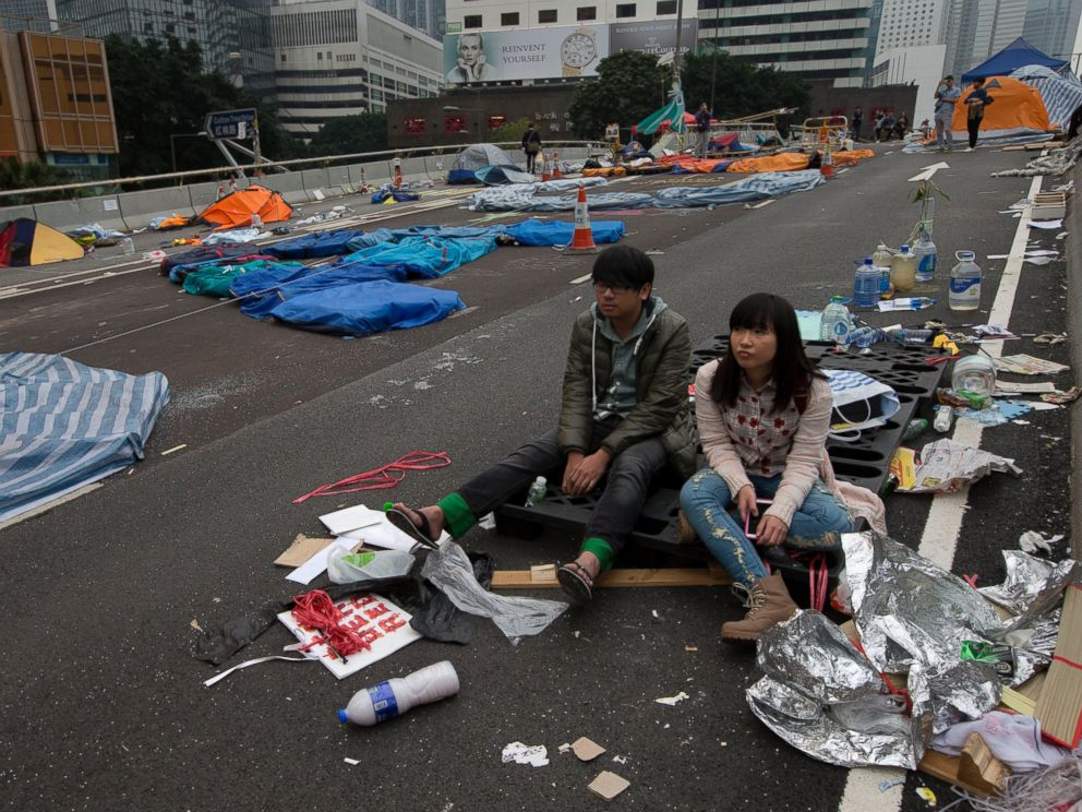 PHOTO: A couple sit at a main road before police clearing barricades and tents outside government headquarters in Hong Kong, Dec. 11, 2014.