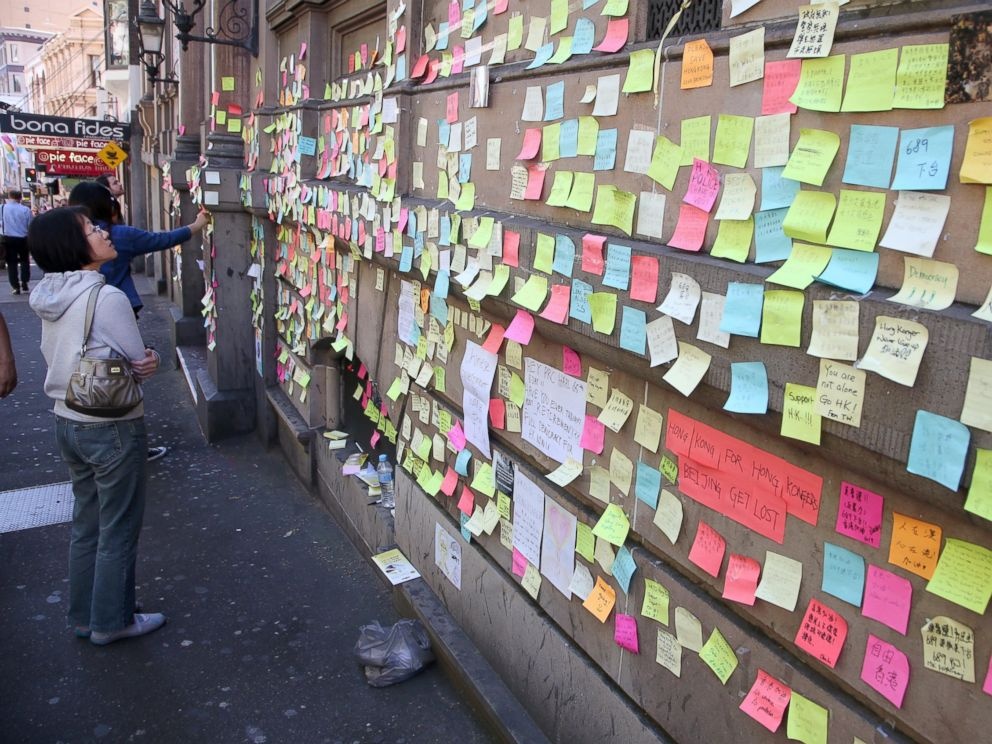PHOTO: A woman looks at colorful post-it notes that are stuck on the outside of the Hong Kong building in Sydney, Oct. 1, 2014, to show support for the pro-democracy protesters in Hong Kong.