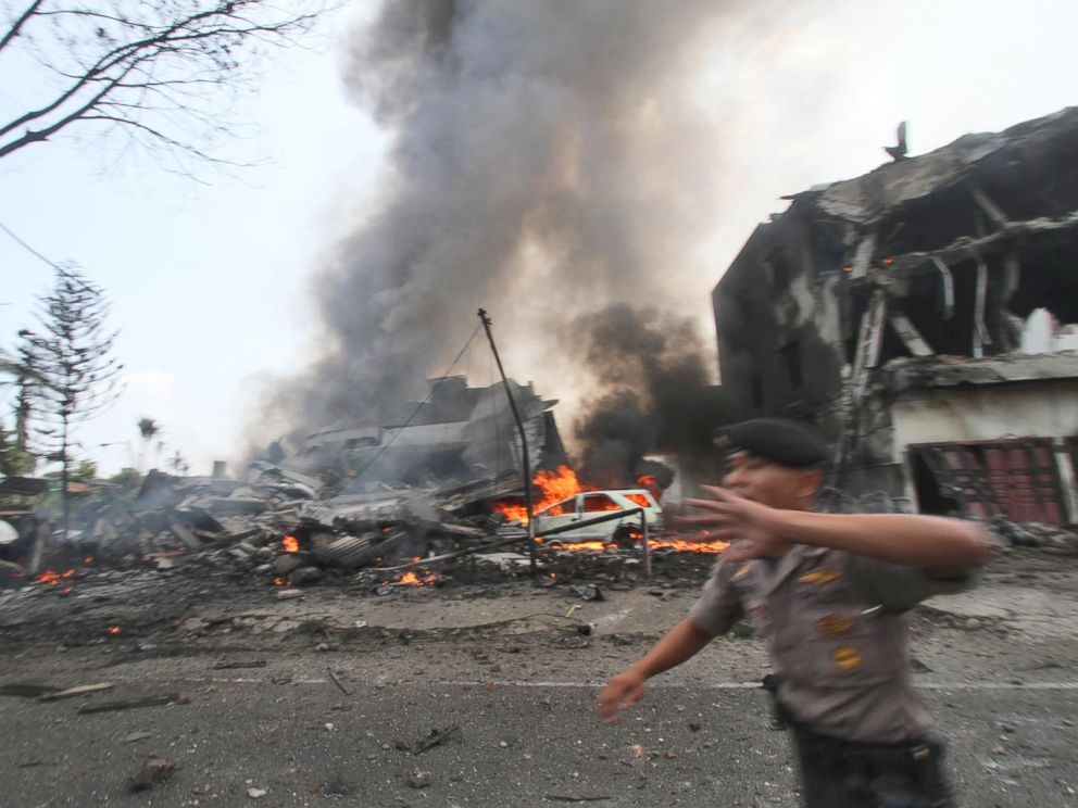 PHOTO: A police officer gestures at the crowd near the site where an Air Force cargo plane crashed in Medan, North Sumatra, Indonesia, June 30, 2015.