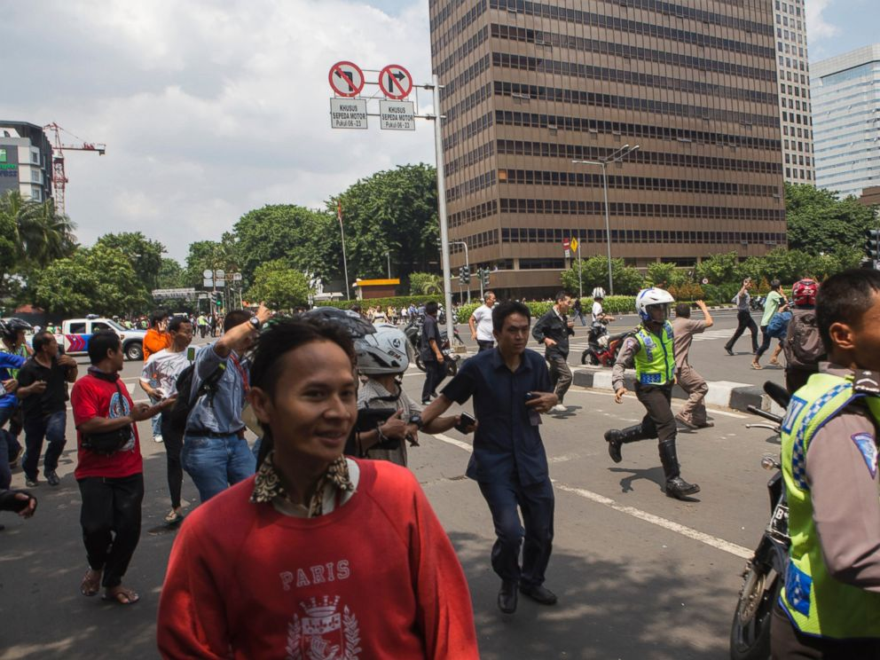 PHOTO: Office workers and unarmed police officers flee from the scene after a gun-battle broke out at the scene of an attack in Jakarta, Indonesia, Jan. 14, 2016.