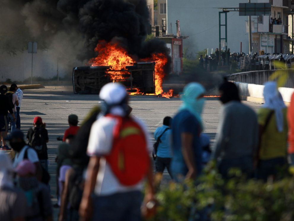 PHOTO: A burning overturned car stands between protesting students and riot police after it was set on fire by protesting college students outside of the Guerrero state capital building in Chilpancingo, Mexico, Oct. 13, 2014.