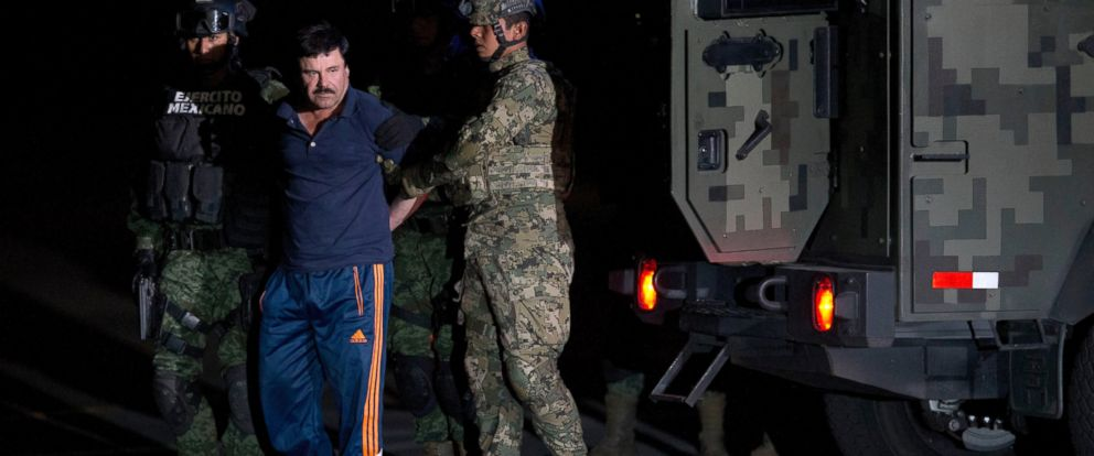 """PHOTO: Mexican drug lord Joaquin """"El Chapo"""" Guzman is escorted by soldiers and marines to a waiting helicopter, at a federal hangar in Mexico City, Friday, Jan. 8, 2016."""