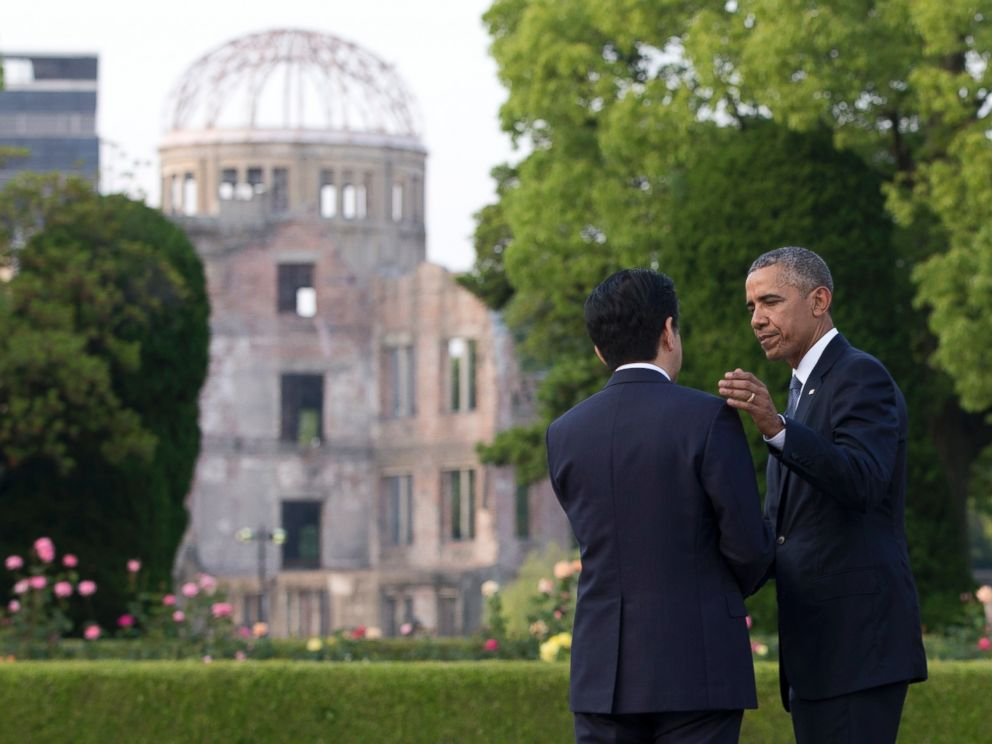 PHOTO: President Barack Obama and Japanese Prime Minister Shinzo Abe speak with the Atomic Bomb Dome seen at rear at the Hiroshima Peace Memorial Park in Hiroshima, western Japan, May 27, 2016.