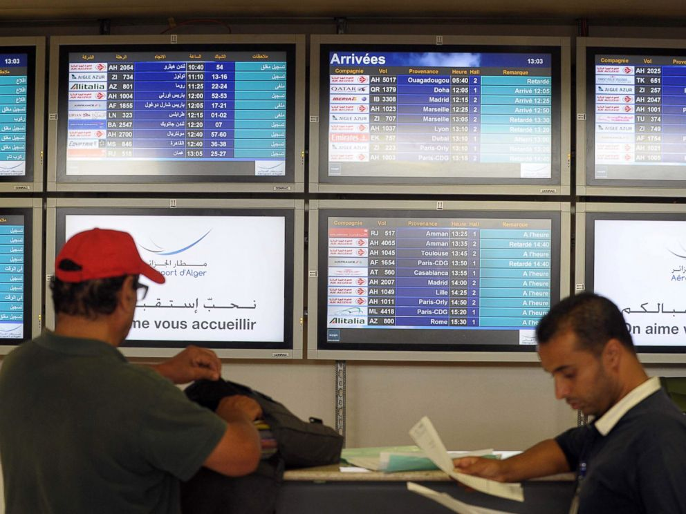 PHOTO: People stand next to an arrival information screen showing the delayed Air Algerie flight 5017 at the Houari Boumediene airport near Algiers, Algeria, July 24, 2014.