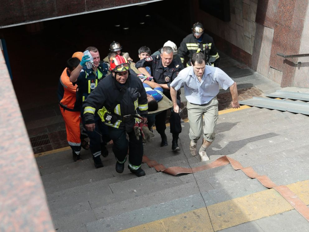 PHOTO: Paramedics, a police officer and a volunteer carry an injured man out from a subway station after a rush-hour subway train derailment in Moscow, Russia, July 15, 2014.