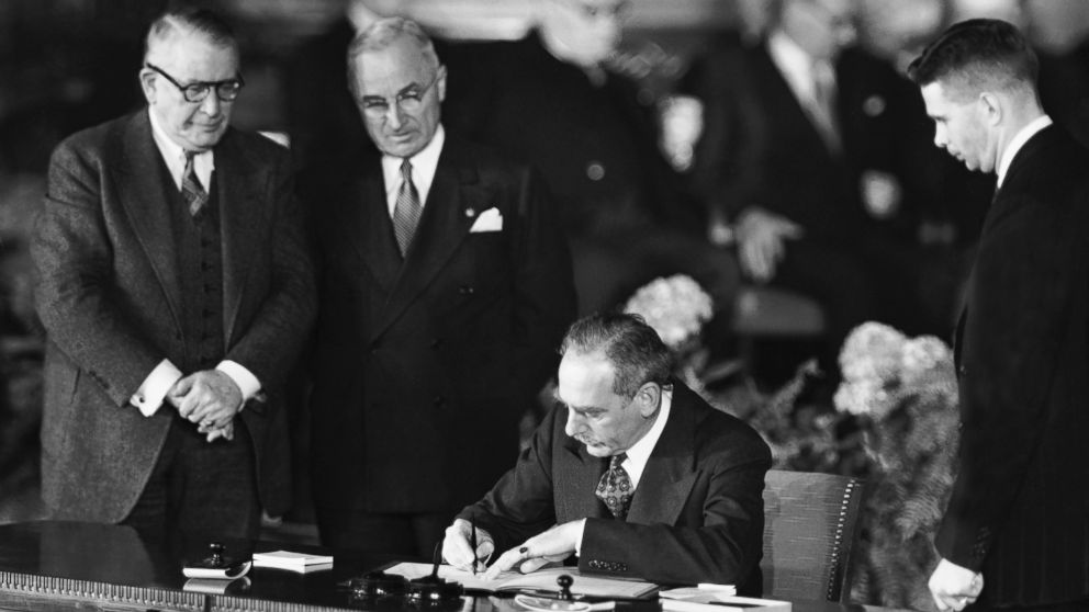 Secretary of State Dean Acheson signs the Atlantic defense treaty for the United States on April 4, 1949.