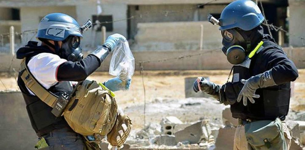 PHOTO: In this Aug. 28, 2013, citizen journalism image provided by the United Media Office of Arbeen which has been authenticated based on its contents and other AP reporting, members of the UN team take samples from sand near a part of a missile.