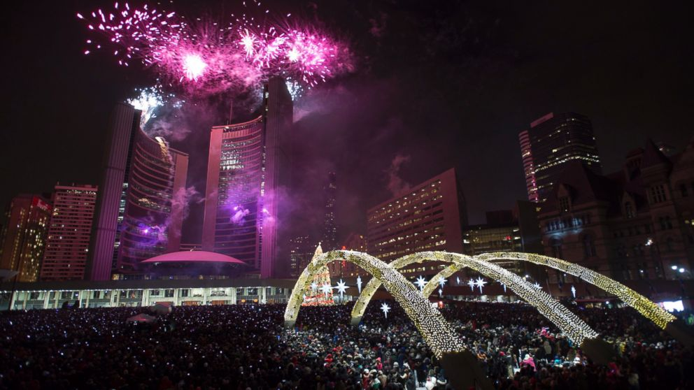 Fireworks explode in front of City Hall as revelers pack Nathan Phillips Square for New Year's celebrations in Toronto on Thursday, Jan. 1, 2015.