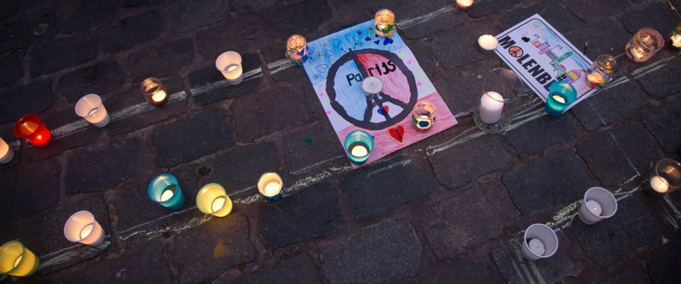 PHOTO: People stand next to candles and banners during a candlelight vigil for the Paris attacks in the town square of Molenbeek, Belgium, Nov. 18, 2015.