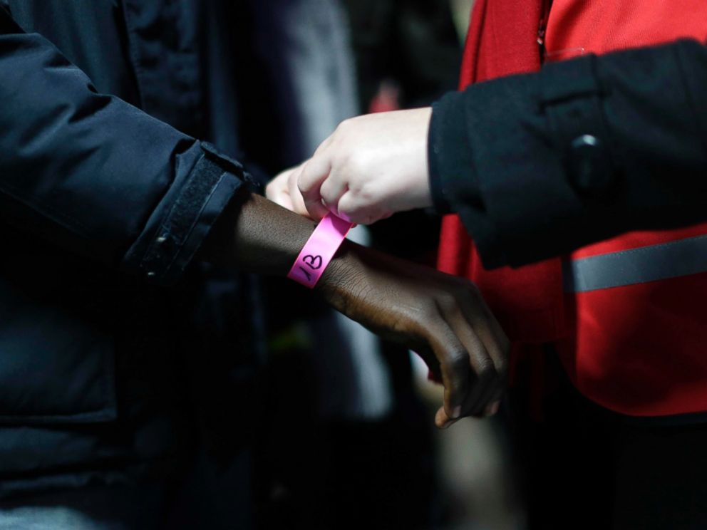 PHOTO: A wristband is attached to a migrant at a processing center in the migrant camp known as the Jungle near Calais, northern France, Oct. 24, 2016.
