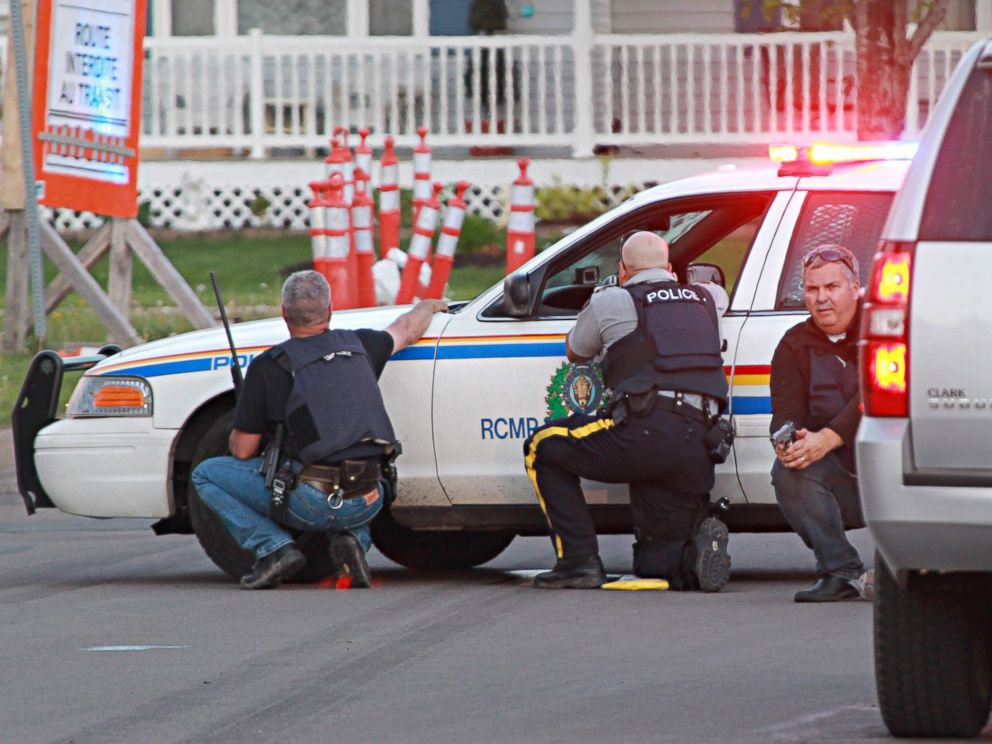 PHOTO: Police officers take cover behind their vehicles in Moncton, New Brunswick, June 4, 2014 following a shooting.