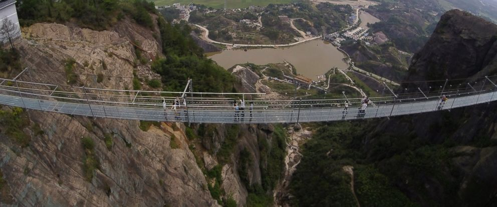 PHOTO: Visitors walk across a glass-bottomed suspension bridge as seen from the air in a scenic zone in Pingjiang county in southern Chinas Hunan province, Sept. 24, 2015.