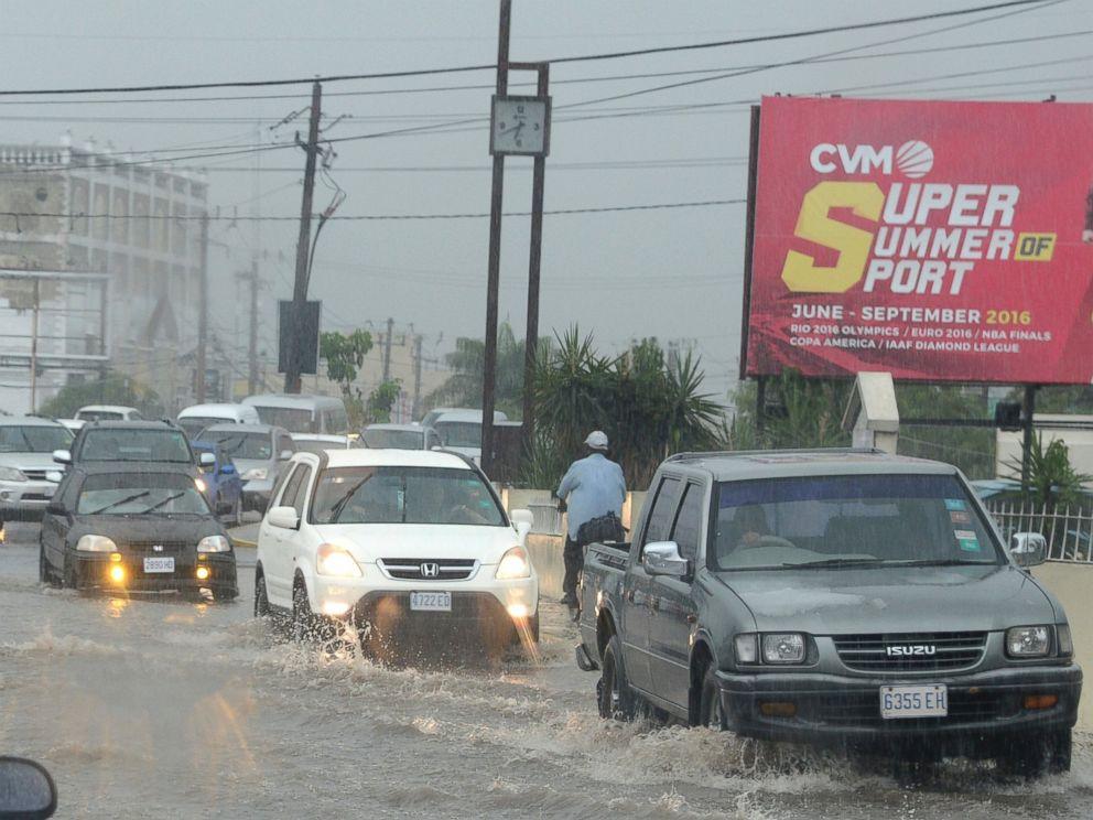 PHOTO: Cars drive along a street under heavy rain in downtown Kingston, Jamaica, Oct. 2, 2016.