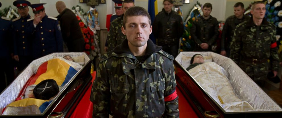 PHOTO: A Ukrainian soldier looks up standing between the coffins of Ukrainian soldier Sergey Kokurin, 35, right, and Russian Cossack militiaman Ruslan Kazakov, 34, left, during their funeral in Simferopol, Crimea, Saturday, March 22, 2014.