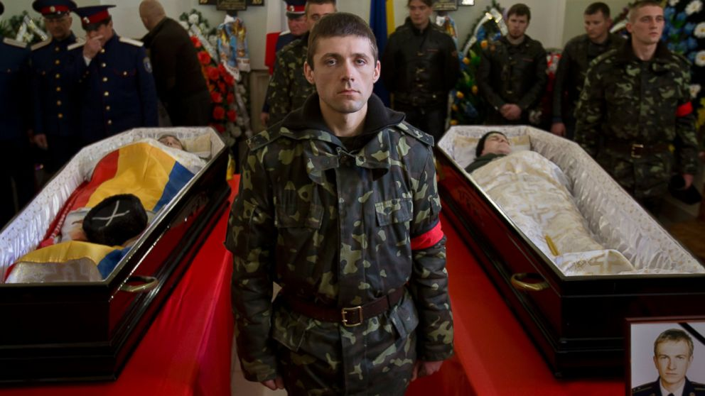 A Ukrainian soldier looks up standing between the coffins of Ukrainian soldier Sergey Kokurin, 35, right, and Russian Cossack militiaman Ruslan Kazakov, 34, left, during their funeral in Simferopol, Crimea, Saturday, March 22, 2014.